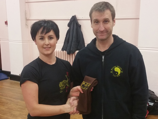 Carly Anderson receiving her Brown Sash from Sifu Derek Dawson