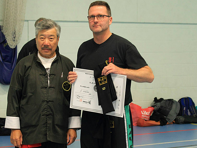 Simon Hugill receiving his Second Degree Black Sash from Master Yau at the BKFA Summer Course