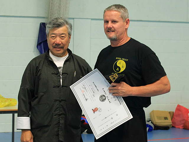 Warrick Bowler receiving his Black Sash from Master Yau at the BKFA Summer Course